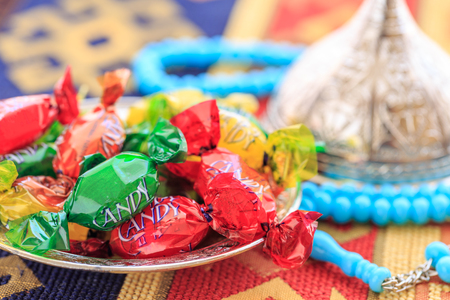 Colorful candies and blue rosary on traditional turkish carpet