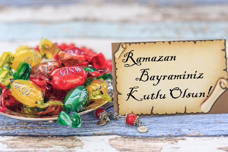 Happy eid al fitr in turkish on the card with candies on vintage table