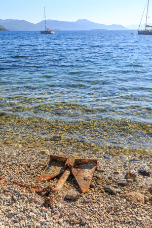 rusts: Rusted old anchor in the coastline of mediterranean sea Stock Photo