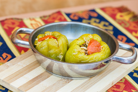 Stuffed green bell peppers in pan on cutting board with turkish carpet