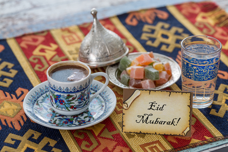 Eid mubarak text  on greeting card with turkish coffee, delights on traditional tablecloth Stok Fotoğraf