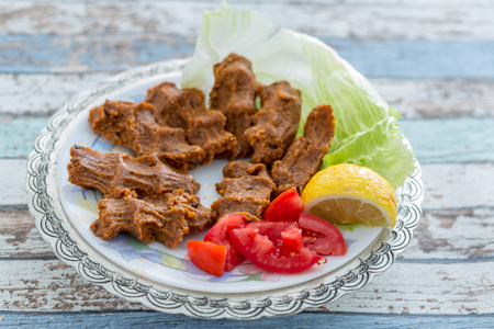 Cigkofte turkish meatball from bulgur with tomato, lemon, and lettuce  side view