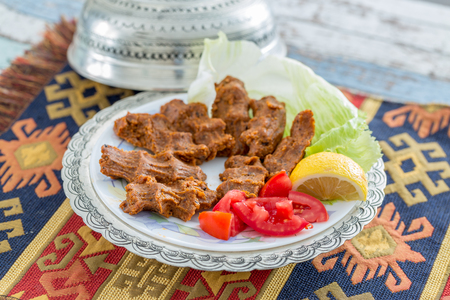 Cigkofte turkish meatball from bulgur with tomato, lemon, and lettuce side view Stock Photo