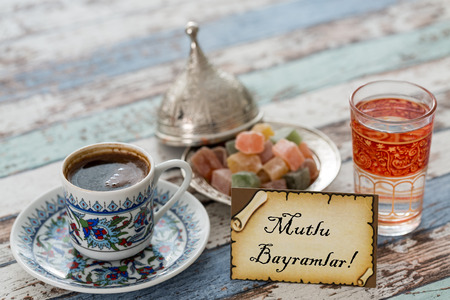Happy eid text in turkish on greeting card with turkish coffee, delights on vintage table
