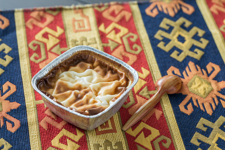 Muhallebi (rise pudding) on traditional carpet with spoon