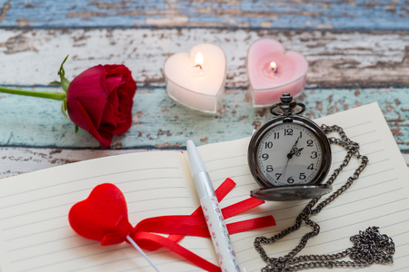 Writing time for love: red rose, journal, pen, and pocket watch with candle lights