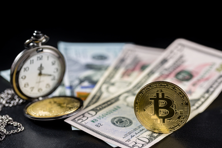 Golden bitcoin standing and retro pocket watch on us dollars with black background