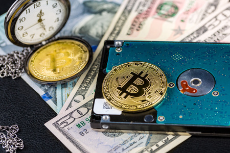 Golden bitcoin on hard disk on us dollars with pocket watch