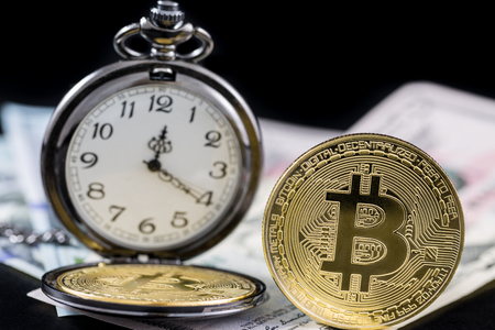 Golden bitcoin and pocket watch near on us dollars with black background