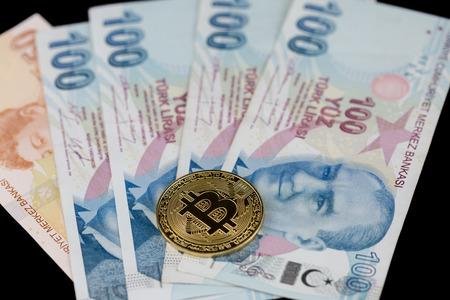 Single golden bitcoin on turkish liras Stock Photo