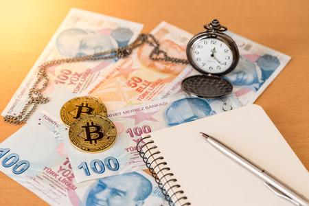 Journal, pen, pocket watch, and two golden bitcoins on turkish liras