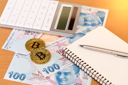 Two golden bitcoins, calculator, journal and pen on turkish paper banknotes