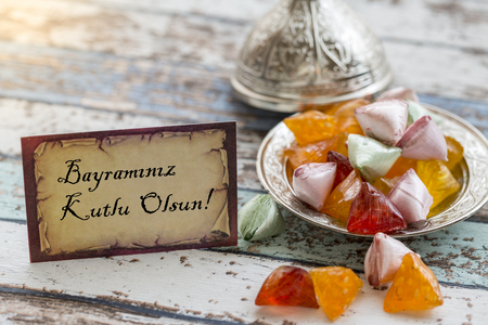 Happy Eid text in turkish on vintage table with candies on metallic plate