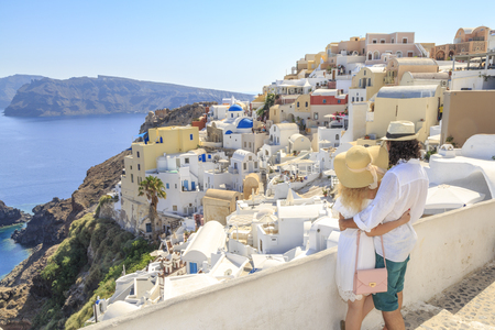 Couple watching the view of cityscape of Oia village in Santorini island, Greece