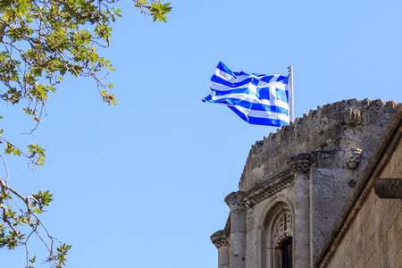 Greek flag on archeological museums top in Rhodes, Dodecanese, Greece