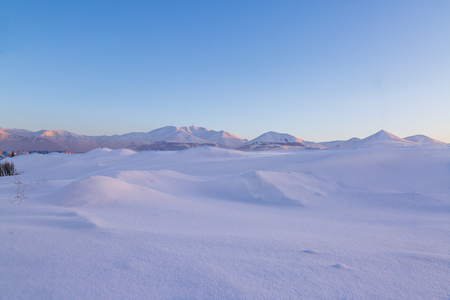 Snow dunes with palandoken mountains background in Erzurum, Turkey Stock Photo