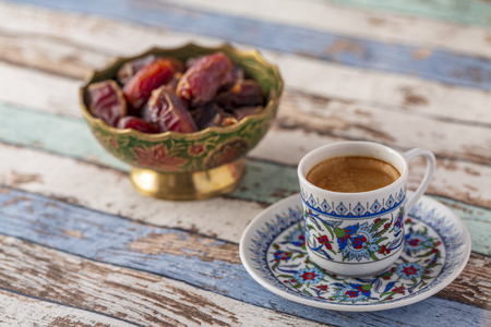 Turkish coffee and dates on turquoise table side view