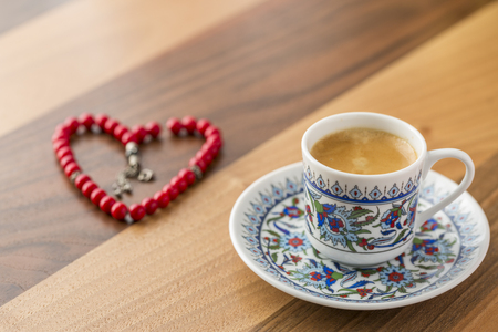 Turkish coffee with heart shaped red rosary on brown table Stok Fotoğraf