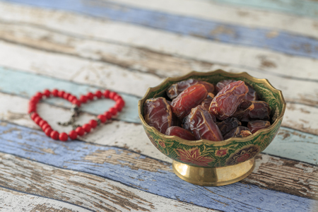 Dates with red heart shaped rosary on turquoise table side view
