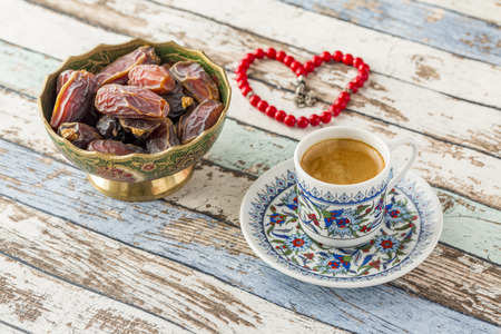 Turkish coffee, dates, and heart shaped rosary on turquoise table side view