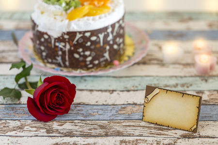 Empty greeting card, single red rose, and birthday cake on turquoise table Stok Fotoğraf