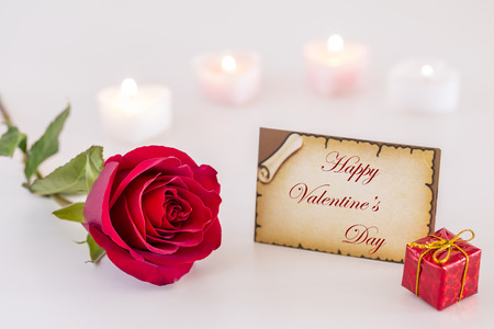 Greeting card with Happy Valentines Day text, single red rose, gift box, and candle light on white