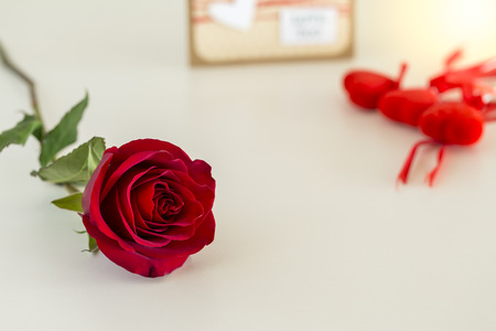 Single red rose, hearts, and card on cream table Stok Fotoğraf