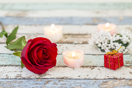 Single red rose, gift box, candles, and white flowers on turquoise table Stok Fotoğraf