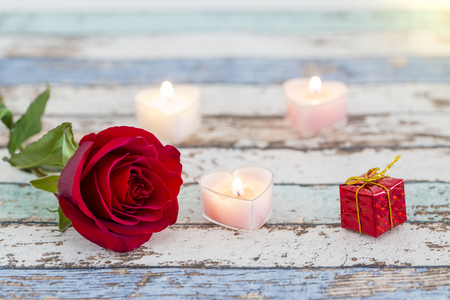 Single red rose, gift box, and candles on vintage table