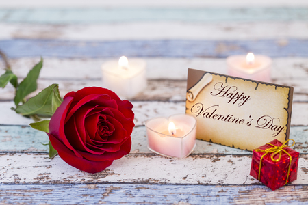 Greeting card with Happy Valentines Day text, red rose, gift box, and candles Stok Fotoğraf