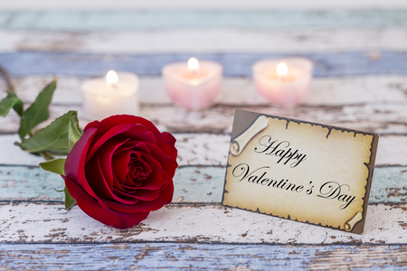 Greeting card with Happy Valentines Day text, single red rose, and candle lights