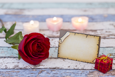 Empty greeting card with single red rose, gift box, and candles