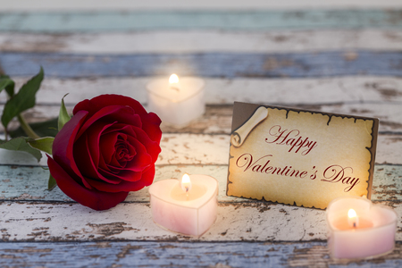 Greeting card with Happy Valentines Day text, single red rose, and candle lights darker