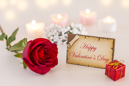 Happy Valentines day text on greeting card with single red rose and candle lights