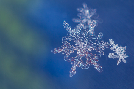 Single snow flake on blue and green background