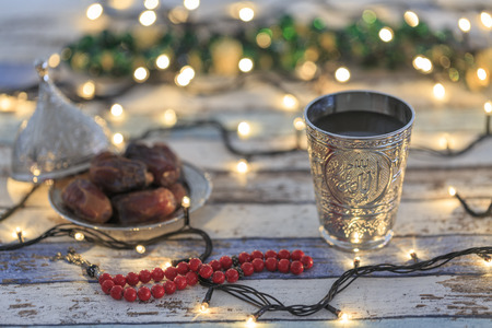 Dates, rosary, and water cup with Allah text in arabic in lights background