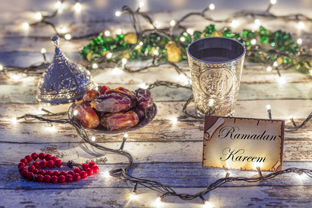 Ramadan Kareem card with dates, rosary, and water cup with Allah writing in arabic in lights background Stok Fotoğraf
