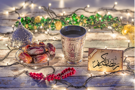 Greeting card with arabic text Ramadan Kareem with dates, rosary, and water cup with Allah text in arabic