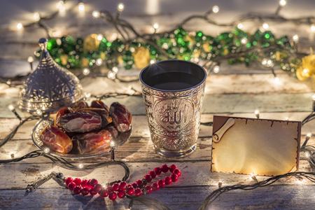 Empty greeting card  with dates, rosary, and water cup with Allah text in arabic