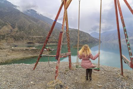Blonde enjoying swing with Tortum lake view in Uzundere, Erzurum, Turkey Stok Fotoğraf