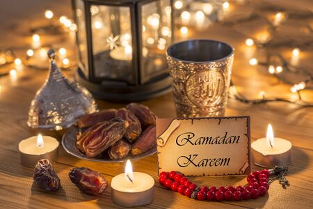 Greeting card Ramadan Kareem with dates, rosary, and metal water cup with Allah text in arabic