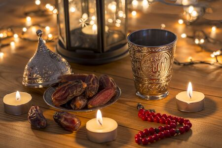 Ramadan concept with dates, rosary, and metal water cup with Allah text in arabic