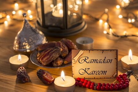 Greeting card Ramadan Kareem with dates, rosary, candles in brown wooden table