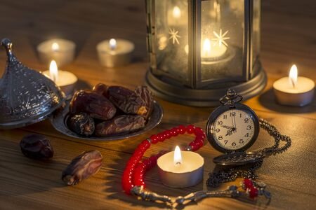Ramadan concept with pocket watch, dates, rosary, lantern, and dates.