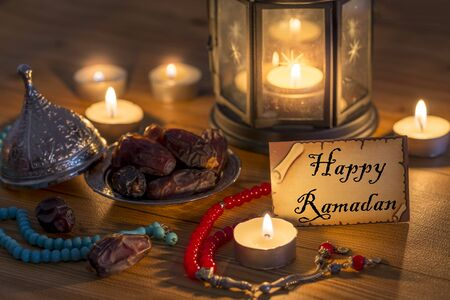 Greeting card writing Happy Ramadan with dates, rosary, candles in brown wooden table