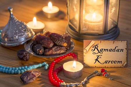 Greeting card writing Ramadan Kareem with dates, rosary, candles in brown wooden table