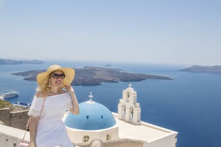Blonde woman near the three bells of Fira church in Fira, Santorini, Greece