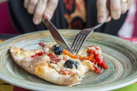 Eating a slice of pizza with fork and knife Archivio Fotografico