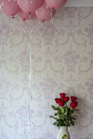 Pink balloons and red roses with pink textured background Archivio Fotografico