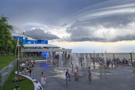 At dolphinarium in Odessa, Ukraine - June 8, 2019 : People having fun at fountain near the dolphinarium with rain clouds in Odessa, Ukraine Editoriali